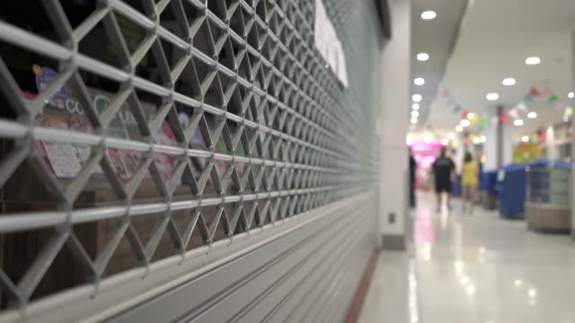 vídeos de stock e filmes b-roll de tilt up of closed shop in shopping mall under coronavirus outbreak - acabar