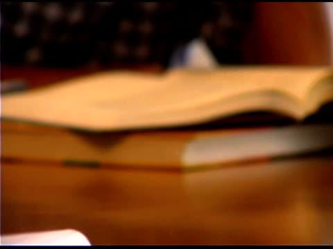 tilt up of frustrated boy reading book - 男児のみ点の映像素材/bロール