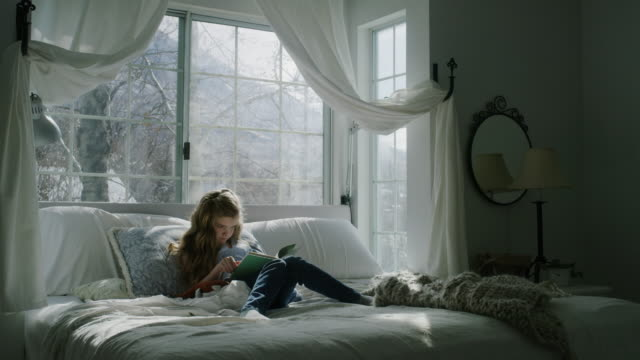 tilt up of girl sitting in bed reading book near bay window / pleasant grove, utah, united states - bay window stock videos & royalty-free footage
