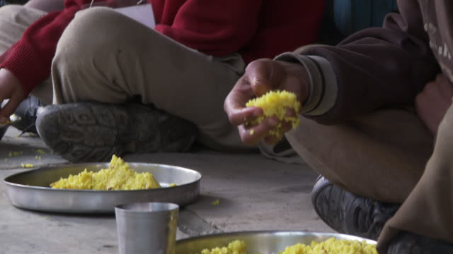 Tilt up of picking up corn rice and eating