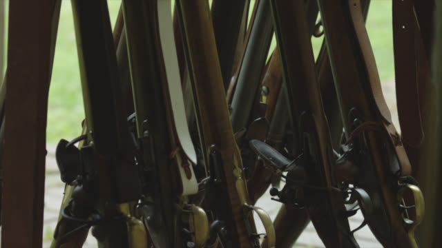 tilt up of rack of historical rifles. - rifle stock videos & royalty-free footage