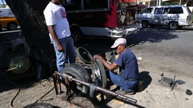 santo domingo dominican republic november 30 2012 a tilt up of two men on the streets of a poor neighbourhood in santo domingo who are changing a tyre - hispaniola stock videos and b-roll footage