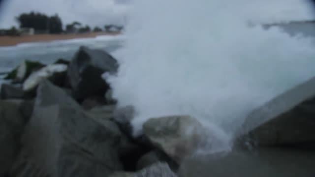 tilt up of waves crashing on rocks/ abidjan/ ivory coast - côte d'ivoire stock videos & royalty-free footage
