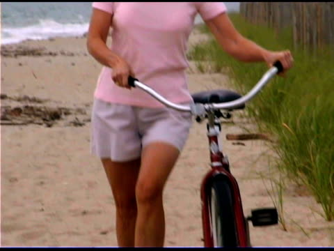 tilt up of woman walking bicycle on beach - 60 64 years stock videos & royalty-free footage
