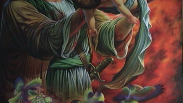 vídeos y material grabado en eventos de stock de tilt up on a painting of hussain ibn ali holding his dead child, who was killed at the battle of kerbala. this type of painting is used in the ashura... - ashura