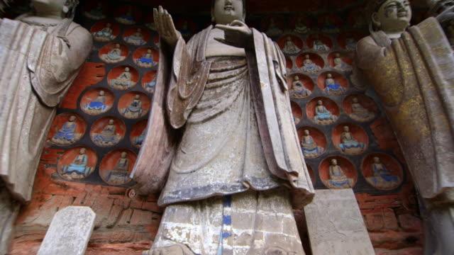 vídeos de stock, filmes e b-roll de tilt up on three beautiful stone statues at the dazu rock carvings in china.  - figura masculina