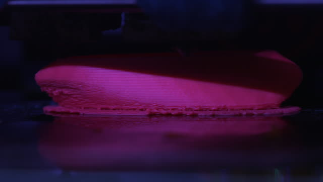 Tilt up onto a close-up shot of a bright pink object being printed by a 3D printer, UK.