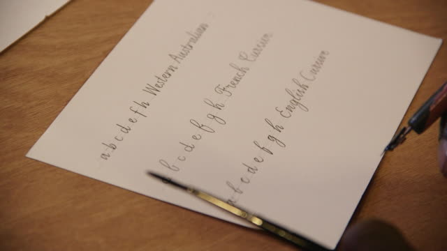 Tilt up onto writing tools poised over a peice of paper displaying three styles of cursive handwriting, UK.