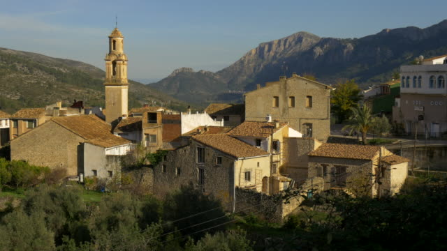 tilt up, orange trees in front of village of La Carroja with church steeple