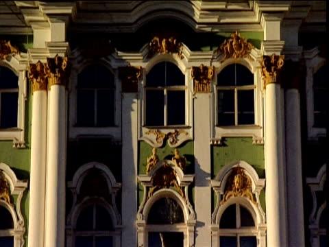 tilt up ornate facade of winter palace (hermitage) to russian flag st petersburg - sankt petersburg stock-videos und b-roll-filmmaterial
