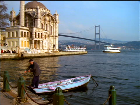 tilt up pan ortakoy mosque with bosporus bridge in background + senior man in rowboat in foreground / istanbul, turkey - july 15 martyrs' bridge stock videos & royalty-free footage