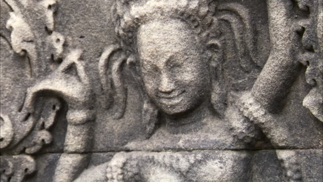 tilt up over carving of dancer, angkor. - relief carving stock videos & royalty-free footage