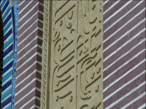 tilt up over persian inscriptions carved onto side of shah jahan mosque - arabic script stock-videos und b-roll-filmmaterial