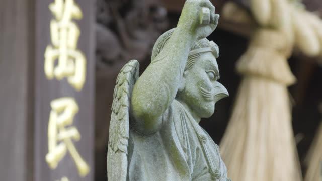 Tilt up over Statue of Karasu tengu outside Takao-san Yakuo-in Yuki-ji on Mount Takao, Japan.