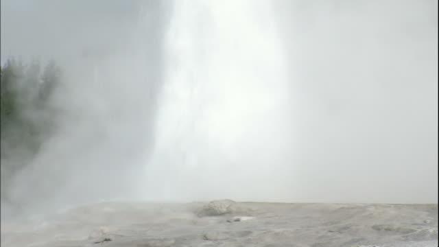 stockvideo's en b-roll-footage met tilt up over steam and water erupting from old faithful geyser - old faithful geiser