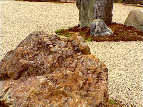 tilt up past large rocks in ryoanji zen rock garden kyoto - chan buddhism stock videos & royalty-free footage