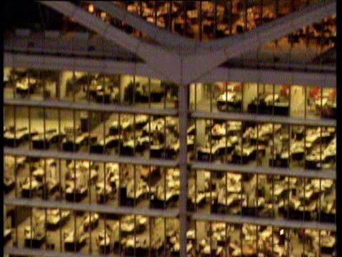 Tilt up past office windows with people working at desks inside Hong Kong