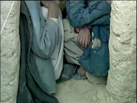 Tilt up people crammed into tiny mud hut in refugee camp; Afghanistan Refugee Crisis 2001