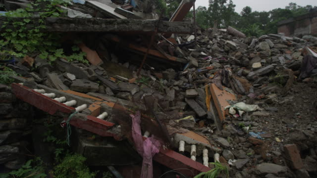 barabise, nepal - july 31, 2015: tilt up piles of rubble, destroyed buildings - rubble stock-videos und b-roll-filmmaterial