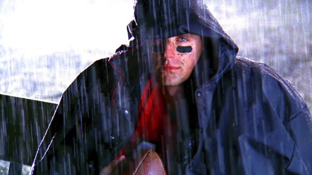 MS tilt up PORTRAIT football player holding ball wearing hooded jacket sitting on bench in rain / zoom in close up