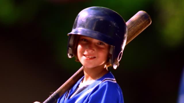 MS tilt up PORTRAIT girl wearing baseball uniform with helmet + swinging baseball bat / Florida