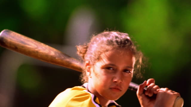 ms tilt up portrait hispanic girl in baseball uniform swinging baseball bat / florida - baseballspieler stock-videos und b-roll-filmmaterial