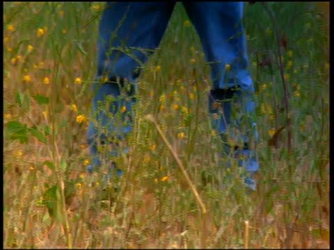 stockvideo's en b-roll-footage met tilt up portrait man wearing undershirt + jeans holding basket of clothing in field - wasmand