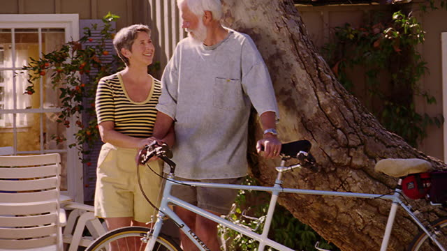 tilt up PORTRAIT middle-aged couple standing by tree outside of house with tandem bicycle