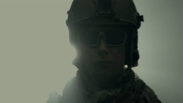 tilt up portrait of soldier in full us army uniform, turn around with silhouette backlight and smoke. - back lit stock videos & royalty-free footage
