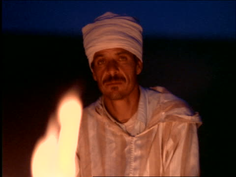 tilt up portrait turbaned middle eastern man sitting by campfire at night / morocco - only mature men stock videos & royalty-free footage