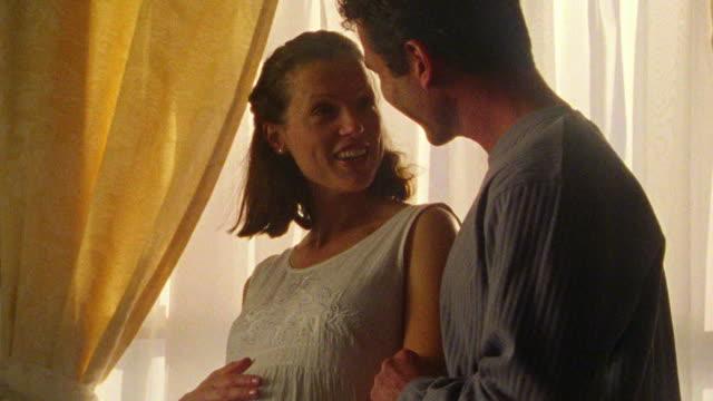 tilt up pregnant woman rubbing stomach in nursery / man enters + rubs stomach with woman - menschlicher bauch stock-videos und b-roll-filmmaterial