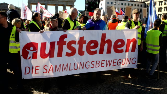 """tilt up, protesters with the banner """"stand up"""" - the collection movement"""" in front of the brandenburg gate. supporters of the new left-wing """"stand... - links platz stock-videos und b-roll-filmmaterial"""
