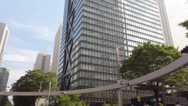 4k tilt up realtime. cityscape office in nishi-shinjuku in tokio, japan. - schrägansicht stock-videos und b-roll-filmmaterial