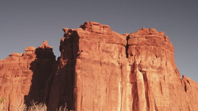tilt up, scenic rock face in barren landscape - rock face stock videos & royalty-free footage