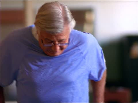 tilt up senior male patient in hospital gown walking in rehab / physical therapy