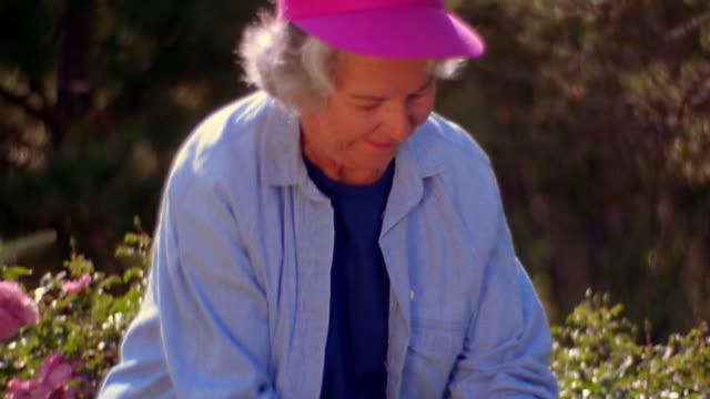 ms tilt up senior woman cutting flower + smelling it with pleased expression - trädgårdshandske bildbanksvideor och videomaterial från bakom kulisserna