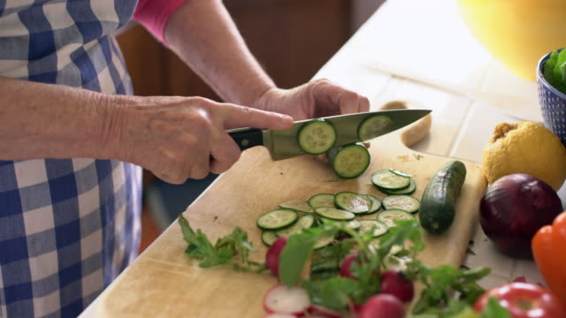 tilt up, cu senior woman cutting vegetables in her kitchen - preparing food stock videos and b-roll footage