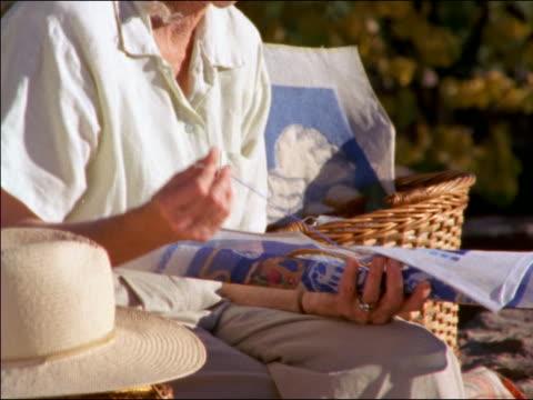 stockvideo's en b-roll-footage met portrait tilt up senior woman sewing on hoop + smiling - hoofddeksel