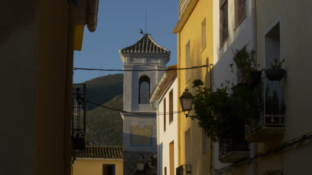 tilt up, shadows in narrow street of old town with church steeple and hills in background