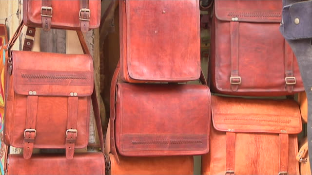tilt up shot leather bags jaisalmer rajasthan india - animal skin stock videos & royalty-free footage