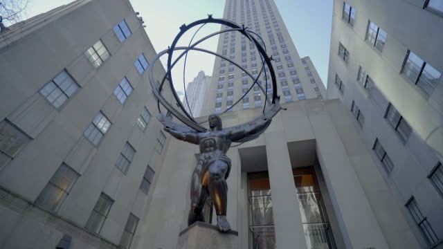 tilt up shot of atlas statue against rockefeller centre in city against sky, low angle view of sculpture by modern building - new york city, new york - rockefeller centre stock videos & royalty-free footage