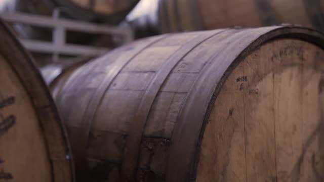 vídeos de stock e filmes b-roll de tilt up shot of barrels on racks at brewery - madeira material