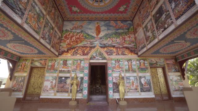 tilt up shot of buddhist mural decoration on wall at temple - vientiane, laos - 壁画点の映像素材/bロール