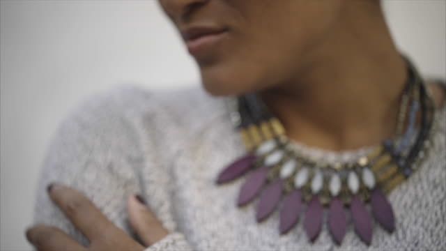 tilt up shot of confident woman wearing sweater and necklace - halskette stock-videos und b-roll-filmmaterial