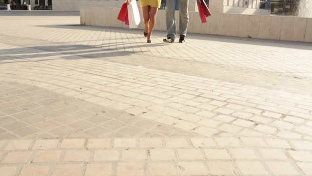 tilt up shot of couple walking in square with shopping bags - 買い物袋点の映像素材/bロール