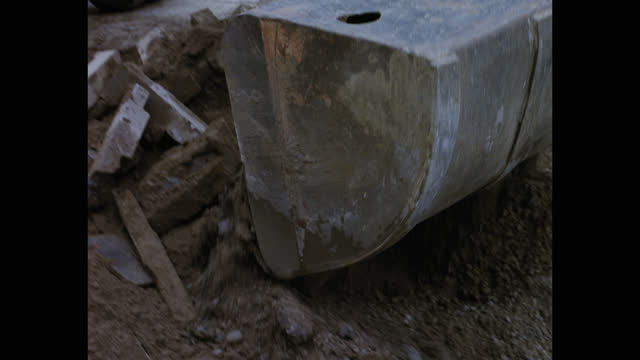 tilt up shot of earth mover digging soil on street - construction vehicle stock videos & royalty-free footage