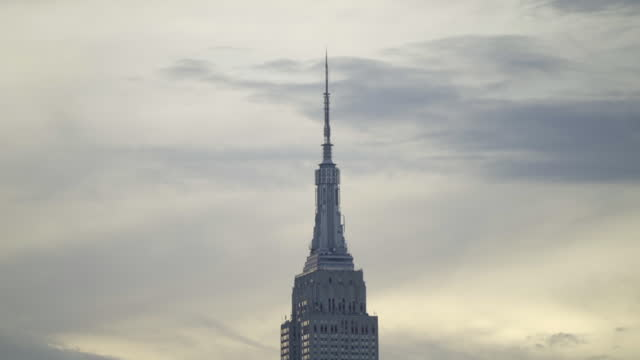 tilt up shot of empire state building in manhattan against sky during sunset - new york city, new york - turmspitze stock-videos und b-roll-filmmaterial