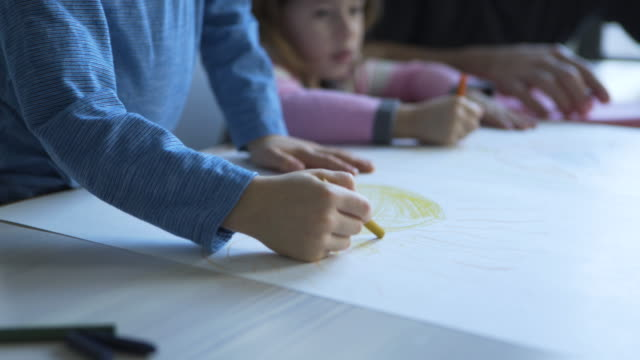stockvideo's en b-roll-footage met tilt up shot of father assisting children in drawing at home - genderblend