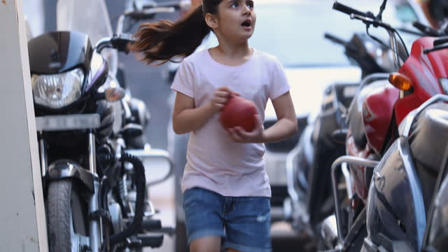 tilt up shot of girl holding piggybank running on road in city - ponytail stock videos & royalty-free footage