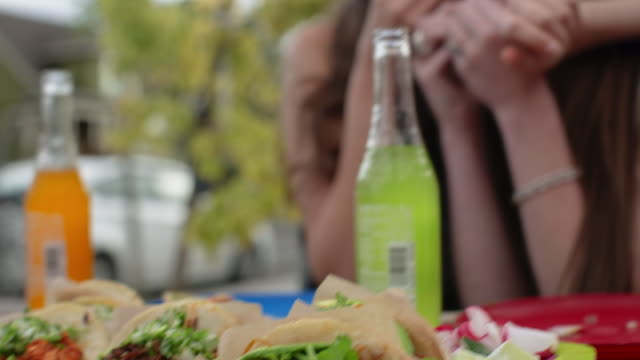 tilt up shot of happy female friends eating lemon slices at sidewalk cafe - taco stock videos & royalty-free footage